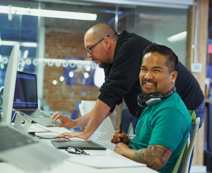2 people working at their computers