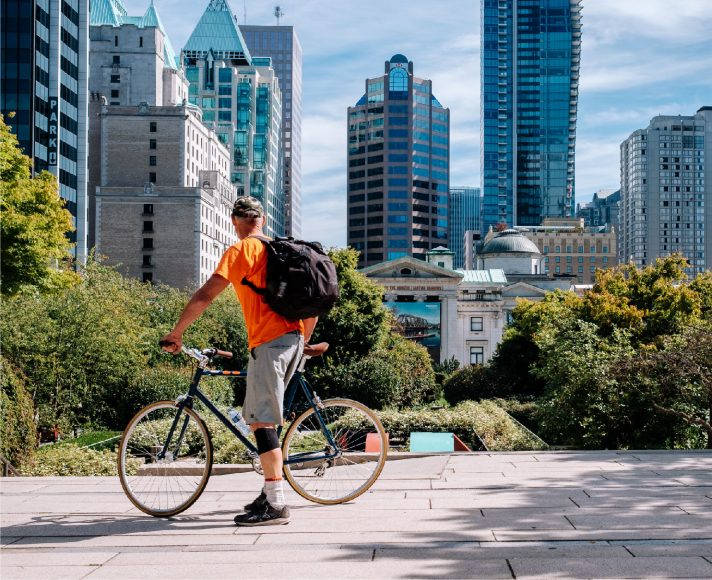 Vancouver Where Lifestyle and Business Come together | Man on a bike in Vancouver looking at the city skyline